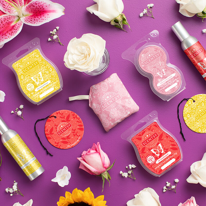 Floral fragrances displayed in Scentsy Bars, Room Spray, Scentsy Pods, a Scent Circle, a Scent Pak and a Fragrance flower. Shown with florals strewn around the products.