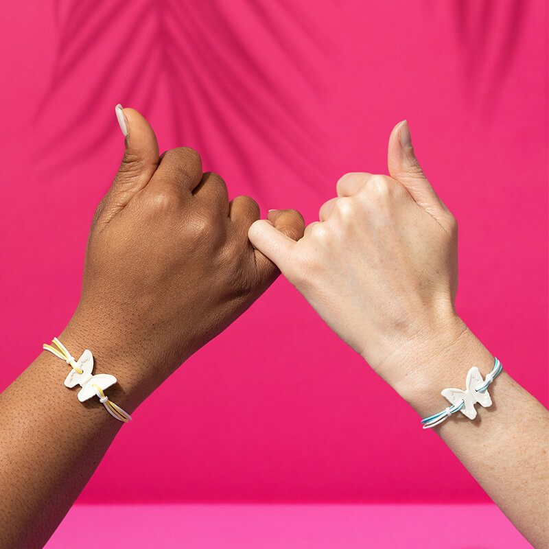 Two hands linking pinkies, both arms wearing the Scentsy Summer Collection Scented Bracelet