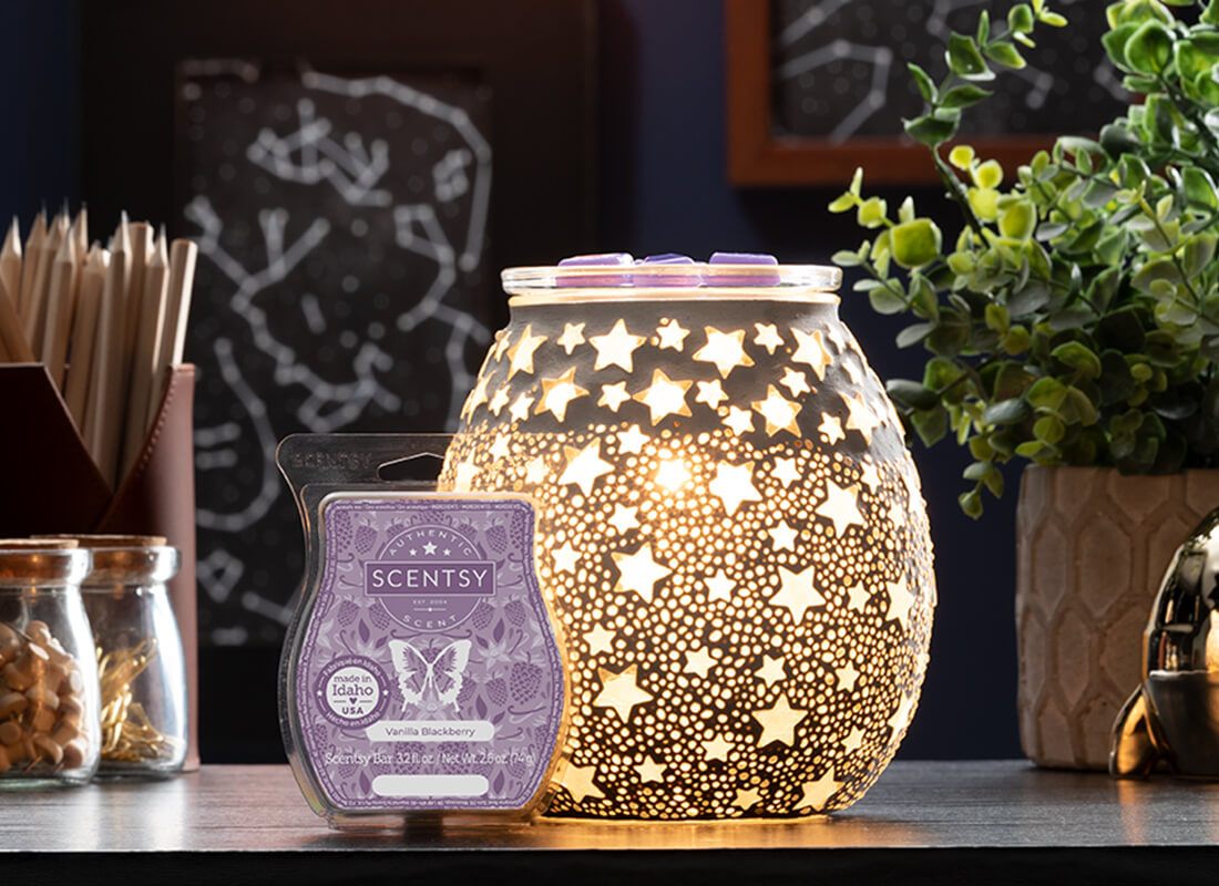 An illustrated Scentsy Bar and warmer in the basket of a hot air balloon. In the background, a bottle of Scentsy Body Wash, Counter Clean and Hand Soap share a basket amid other hot air balloons floating through the sky.