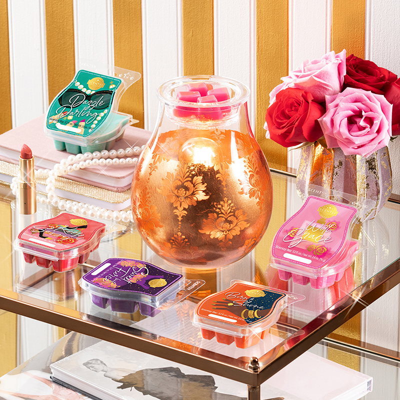 The Glamour Time Warmer is displayed on a side table surrounded by the Glamorous You Scentsy Bars, a stack of notebooks, a pearl necklace, a tube of lipstick and a vase of roses.