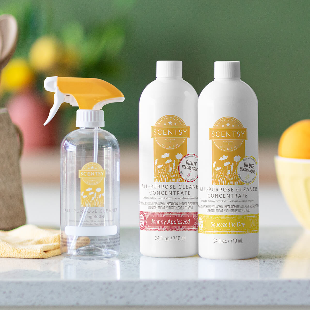 A clear Scentsy mixing bottle and two All-Purpose Cleaner Concentrates in Johnny Appleseed and Sqeeze the Day sit on a daylit kitchen counter.