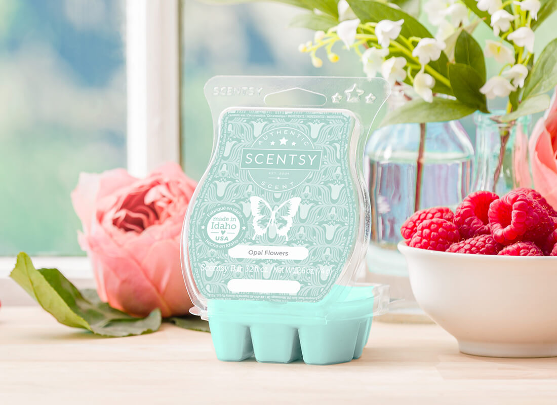 An Opal Flowers Scentsy Bar sits open on a windowsill next to a vase of lily of the valley, surrounded by raspberries and roses.
