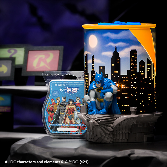 The Batman – Scentsy Warmer glows next to a DC Justice League – Scentsy Bar in a dark scene reminiscent of the Bat Cave.