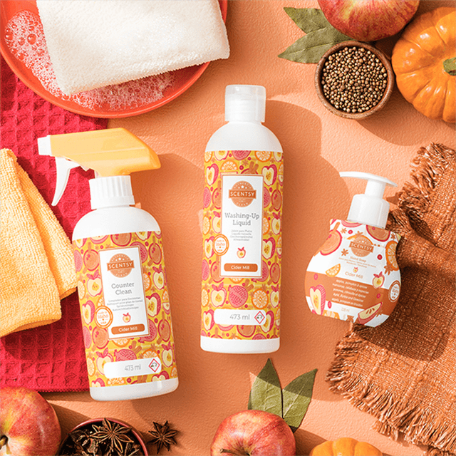Bottles of Autumn Road Trip Counter Clean, Dish Soap and Hand Soap are displayed on a table surrounded by autumn fruits, leaves, dish towels and decorative dishes.
