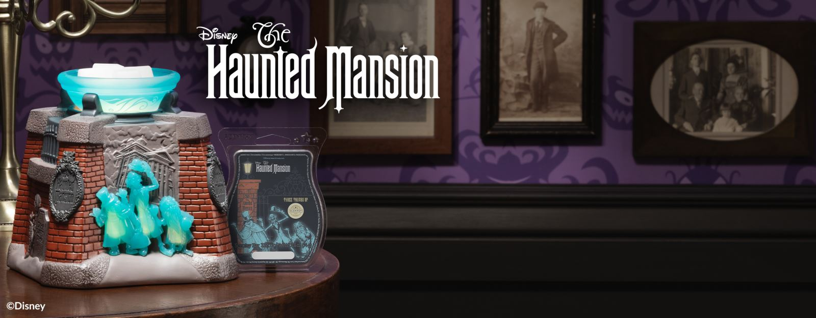 The Disney Haunted Mansion – Scentsy Warmer and Disney Haunted Mansion: Three Thumbs Up – Scentsy Bar are displayed on a table with vintage photos and spooky wallpaper in the background.